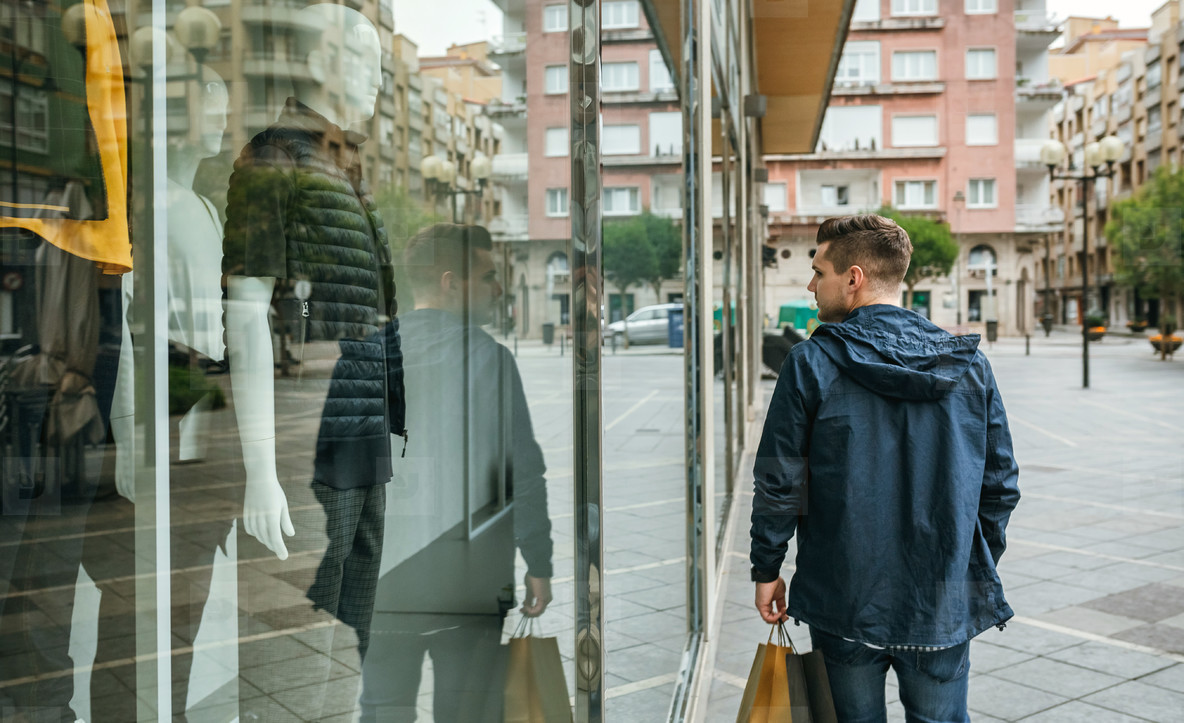 Man with shopping bags in front clothing store