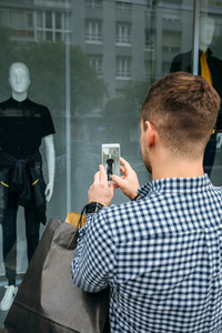 Man taking a photo of a shop window of a fashion store