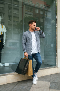Young man with shopping bags and mobile
