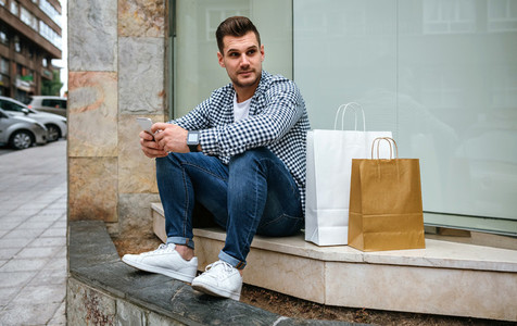 Young man with shopping bags sitting