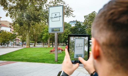 Man taking photo with tablet to customizable advertising poster