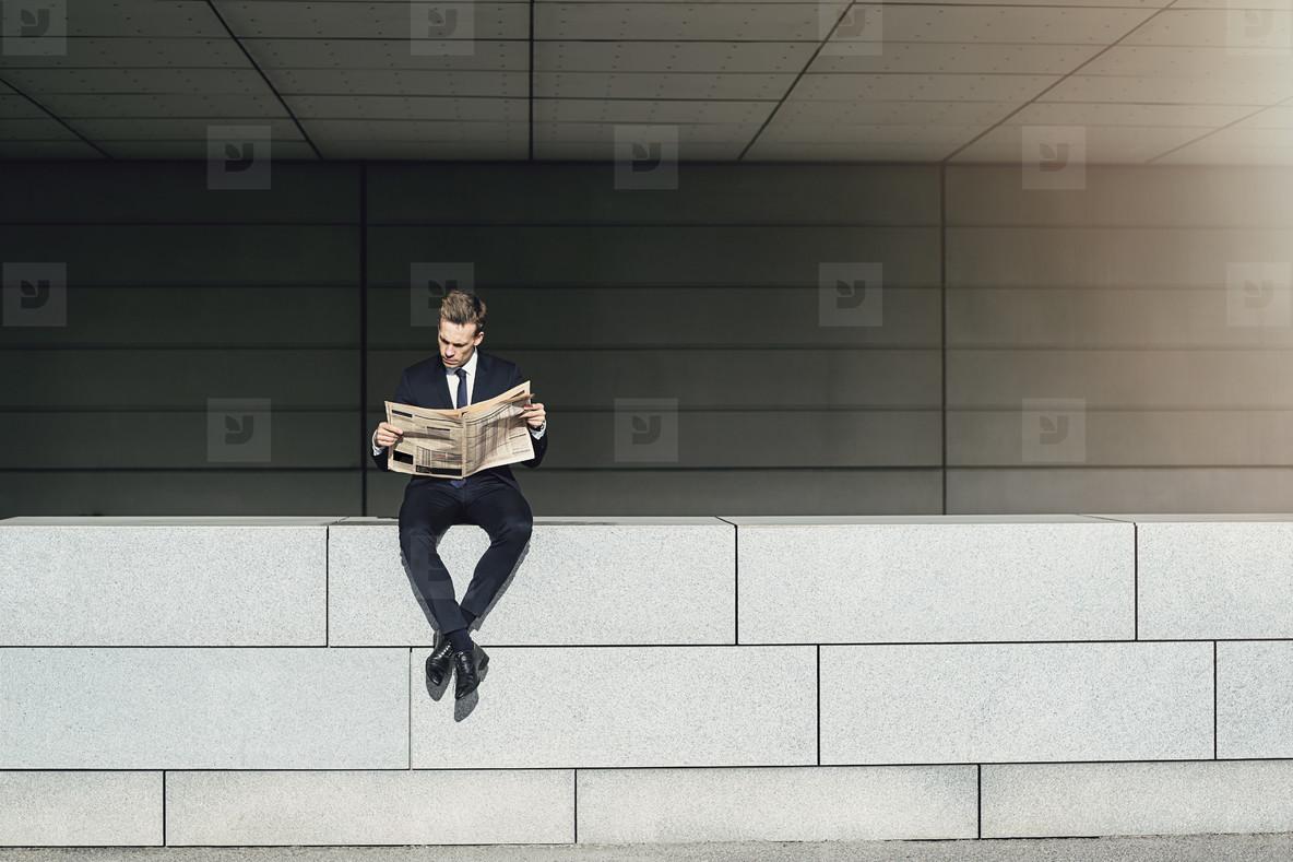 Businessman sitting on brickwall and reading newspaper