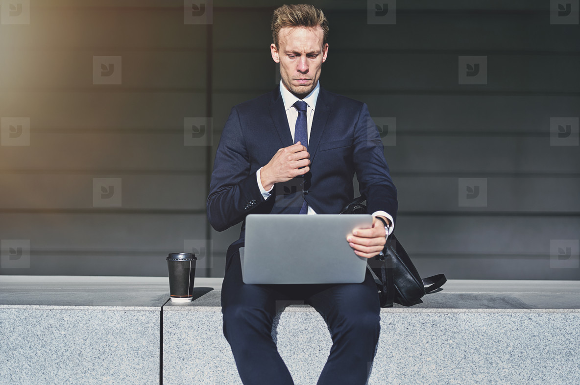 Serious handsome businessman turning on his laptop