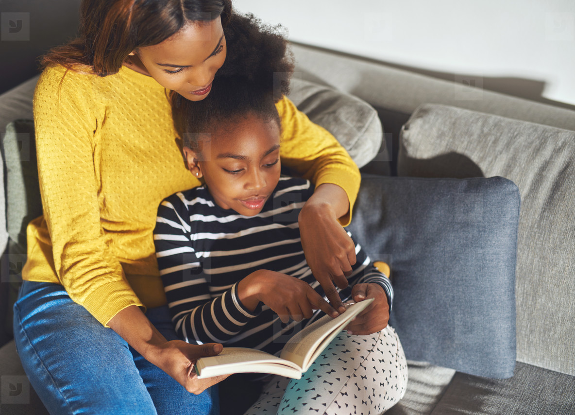 Black mom learning daughter to read