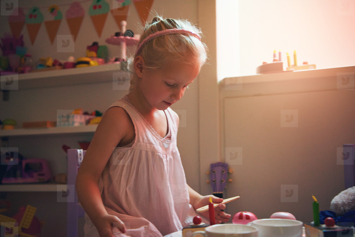 Girl playing tea party looking at toy cake