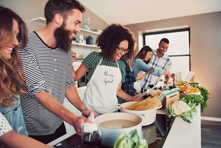 Large group of six friends cooking pasta at table