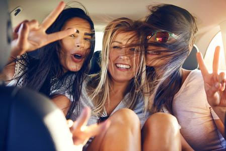 Three beautiful female friends make peace signs