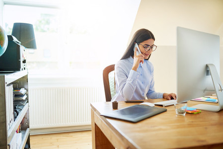 Small business owner on phone at desk