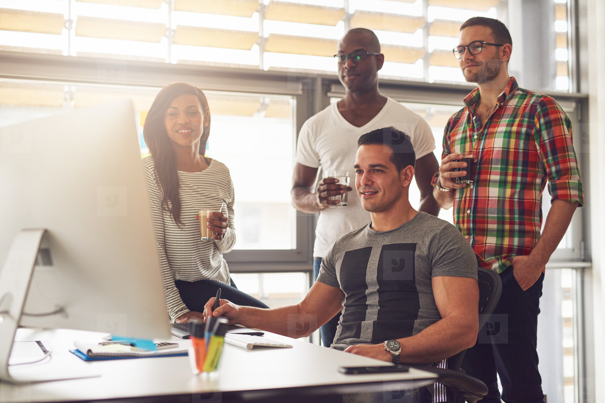 Relaxed young workers around computer in office
