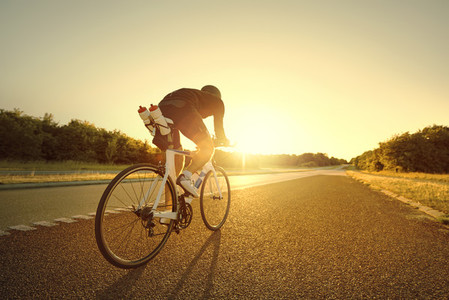 Man taking a bike ride in sunset