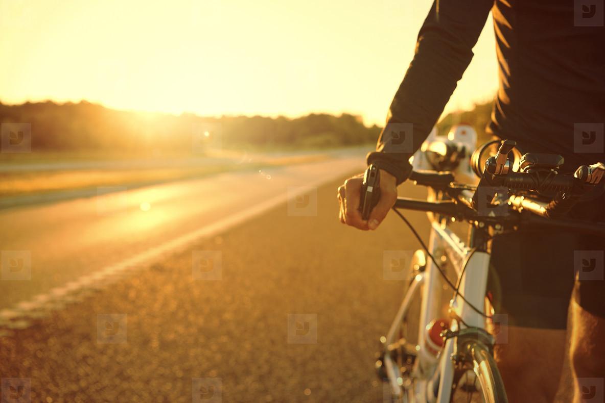 Sportsman holding a bike and havingrest