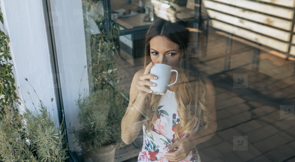 Woman behind the window drinking coffee