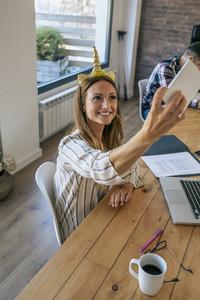 Businesswoman taking selfie with unicorn headband
