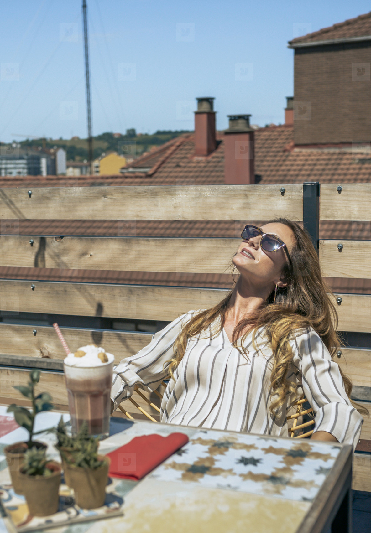 Woman with sunglasses sunbathing on the terrace