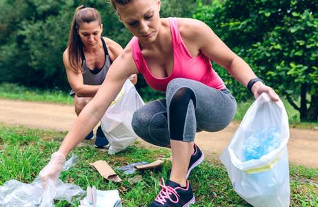 Women picking up trash doing plogging