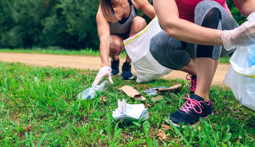 Women picking up trash doing plogging