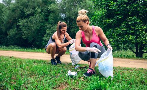 Girls with garbage bag doing plogging
