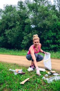 Girl picking up trash doing plogging