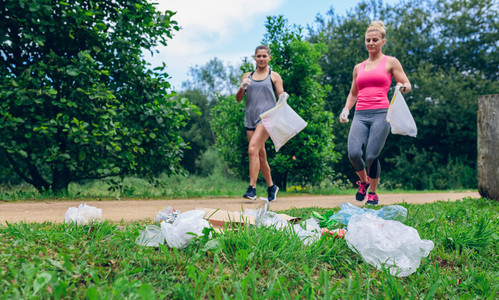 Waste pile and two girls doing plogging