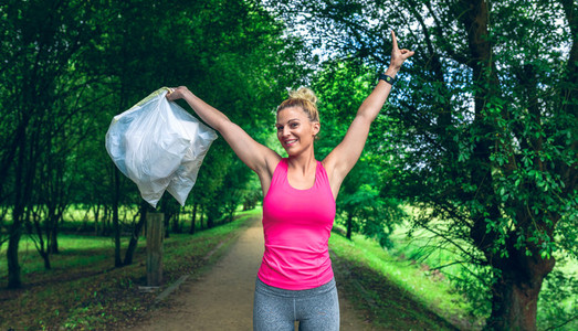 Girl arms up showing garbage bags doing plogging