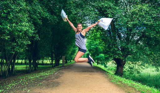 Girl jumping with trash bags after plogging