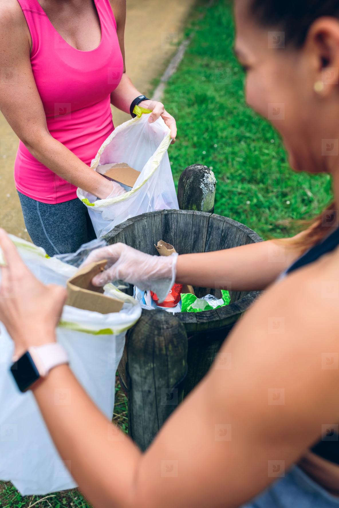 Two girls throwing garbage after plogging