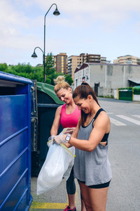 Girls throwing garbage to recycling dumpster
