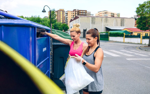 Girls throwing garbage to recycling dumpster