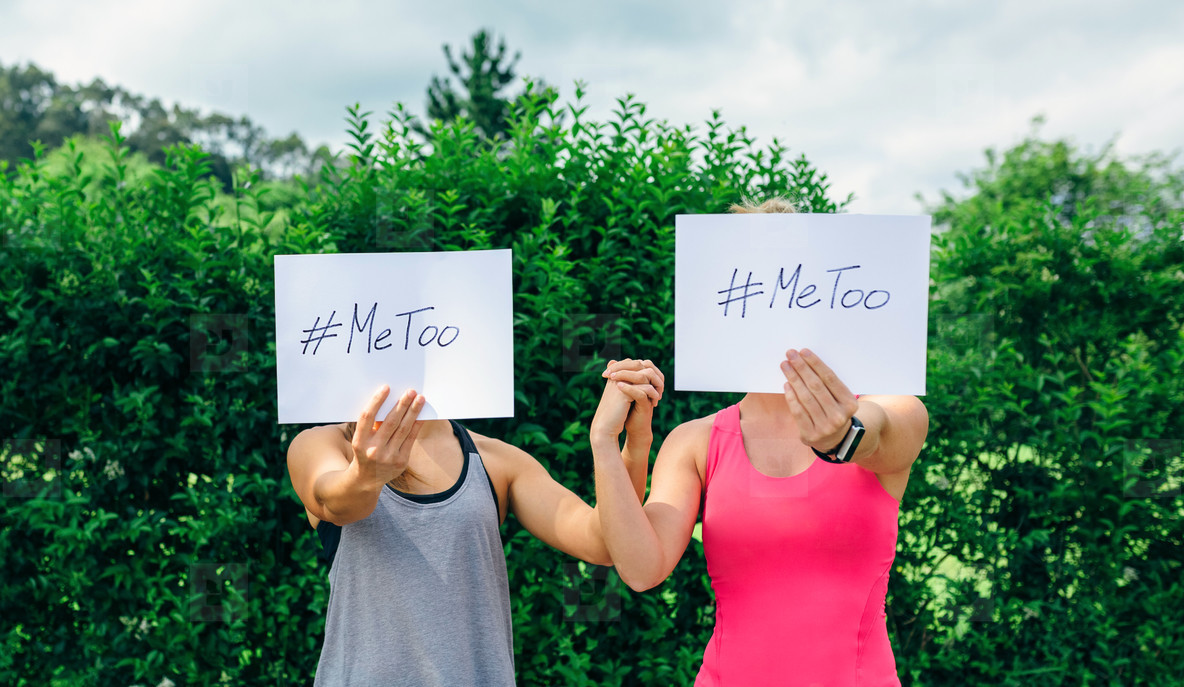 Women showing poster with metoo hashtag