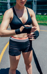Sportswoman putting on boxing bandages