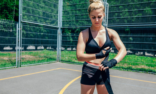 Sportswoman putting on boxing bandages