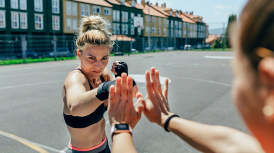Sportswoman training boxing with her trainer