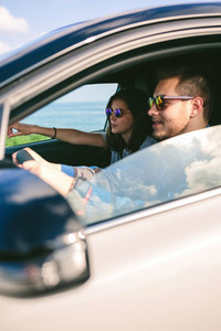 Young man driving a car with his girlfriend