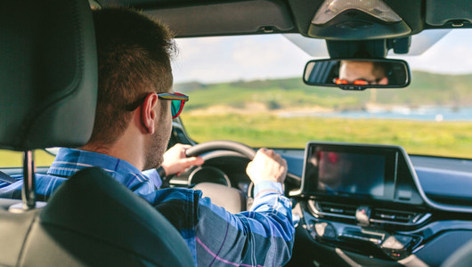 Young man holding steering driving