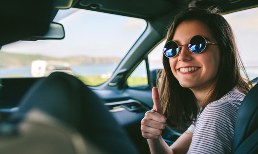Girl doing thumbs up in the car