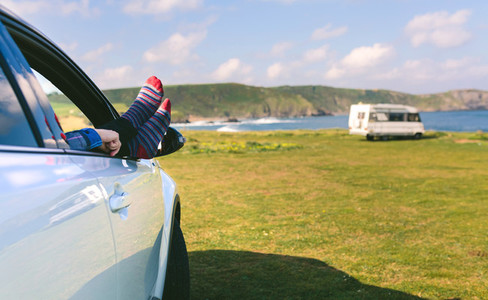 Unrecognizable man resting feet up sitting on the car
