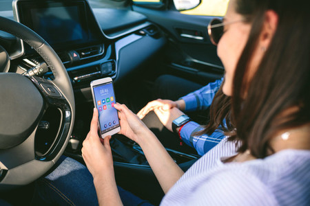 Girl and boyfriend using mobile in the car