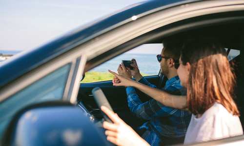 Couple taking picture of landscape from the car