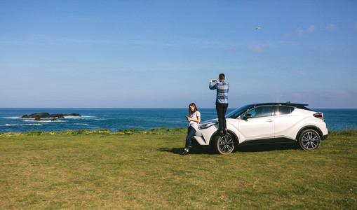 Couple traveling by car photographing the landscape
