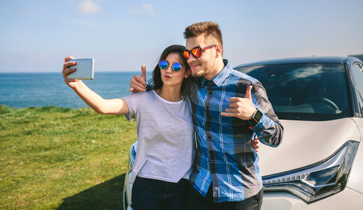 Young couple doing a selfie on the car