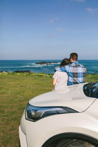 Couple with car watching landscape