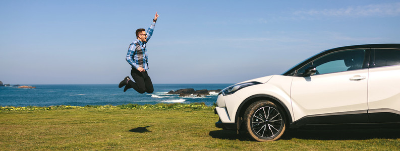 Young man jumping happy with car
