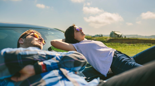 Young couple lying on the windshield