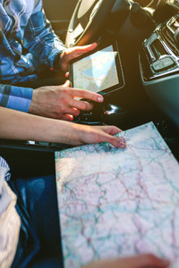 Couple comparing paper map and a gps navigator