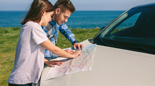 Couple looking at a map leaning on the car