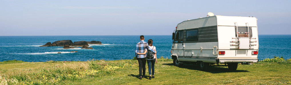 Couple taking a walk near the coast with a camper