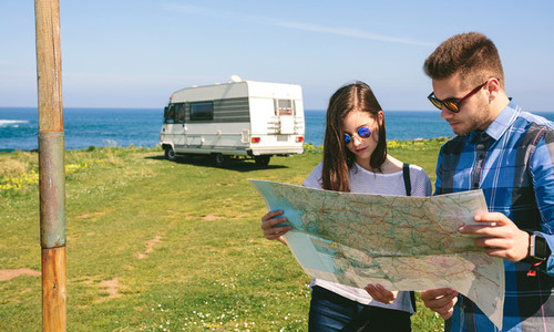 Young couple looking a map near the coast