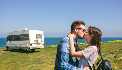 Couple kissing near the coast with a camper