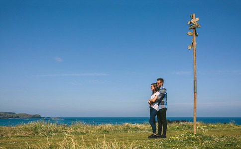 Couple embraced by a direction sign
