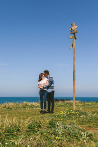 Couple kissing embraced by a direction sign